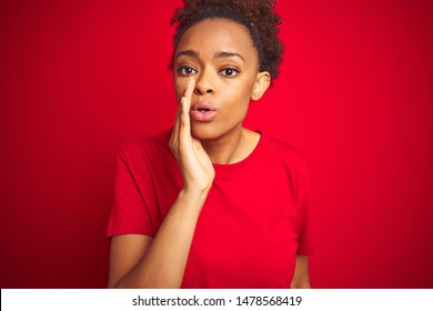 Young beautiful african american woman with afro hair over isolated red background hand on mouth telling secret rumor, whispering malicious talk conversation