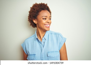 Young beautiful african american woman with afro hair over isolated background looking away to side with smile on face, natural expression. Laughing confident.