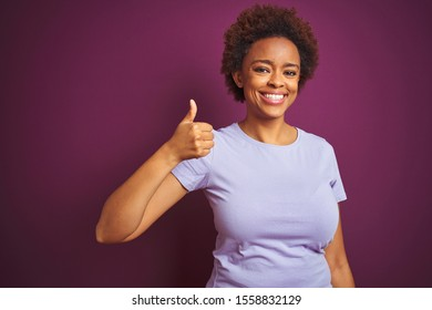 Young beautiful african american woman with afro hair over isolated purple background doing happy thumbs up gesture with hand. Approving expression looking at the camera showing success.