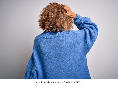 Young beautiful african american woman wearing turtleneck sweater over white background Backwards thinking about doubt with hand on head
