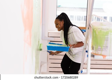 Young beautiful African American woman painting wall in her new apartment. Renovation and redecoration concept.
