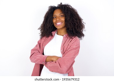 young beautiful African American woman wearing pink jacket against white wall happy face smiling with crossed arms looking at the camera. Positive person.