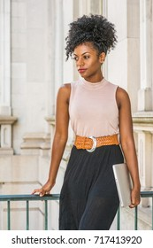 Young beautiful African American woman with afro hairstyle wearing sleeveless light color top, belt, black skirt, holding laptop computer, standing in vintage office building in New York, thinking.