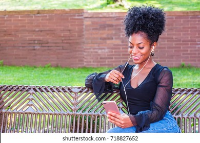 Young beautiful African American Woman with afro hairstyle wearing mesh sheer long sleeve shirt blouse, sitting on bench at park in New York, listening music with earphone and cell phone, smiling.
