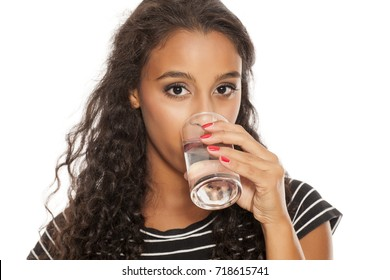 young beautiful african girl drinking water from a glass on white background