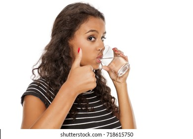 young beautiful african girl drinking water from a glass and  showing thumbs up on white background