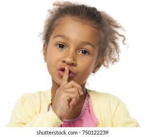 Young beautiful african Little girl has put forefinger to lips as sign of silence, isolated on white background