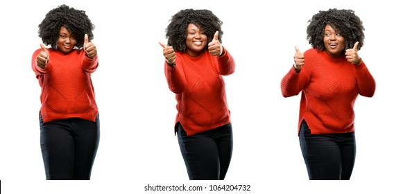 Young beautiful african plus size model stand happy and positive with thumbs up approving with a big smile expressing okay gesture isolated over white background. Collection composition