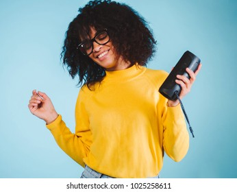 Young beautiful african woman enjoying and dancing at blue background. Modern trendy girl with afro hairstyle listening to music by wireless portable speaker.