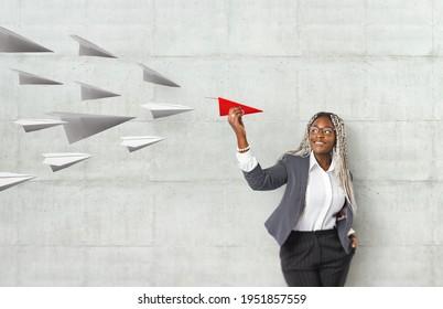 Junge schöne Afrikanerin, die ein Papierflieger mit Handmodell hält