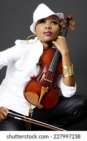 Young Beautiful African Woman Posing with a Violin, Fashion, Studio Shot, on Gray Background