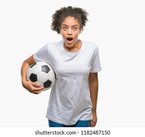 Young beautiful afro american holding soccer football ball over isolated background scared in shock with a surprise face, afraid and excited with fear expression
