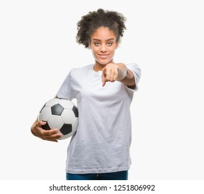 Young beautiful afro american holding soccer football ball over isolated background pointing with finger to the camera and to you, hand sign, positive and confident gesture from the front