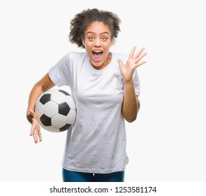 Young beautiful afro american holding soccer football ball over isolated background very happy and excited, winner expression celebrating victory screaming with big smile and raised hands