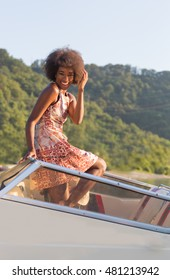 Young beautiful afro american woman in colorfull dress is posing on the yacht boat near the beach on lake