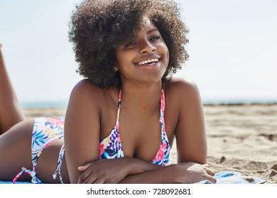 Young beautiful afro american woman lying on beach