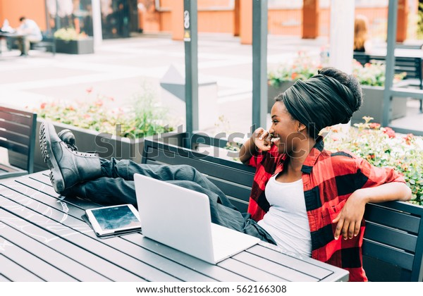 Young beautiful afro black woman sitting outdoor with legs on the table, relaxed, using computer and tablet, smiling - working, business, studying concept