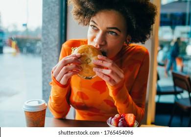Junge schöne Afro Frau im Restaurant mit Hamburger beißen - Hungrige vielfältige Frau im Restaurant essen Bagel