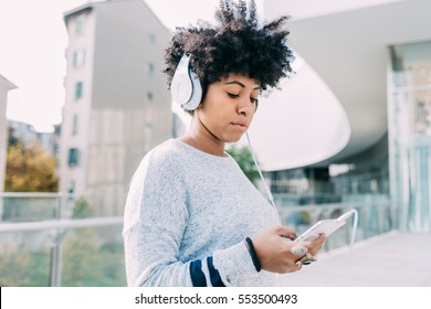 Young beautiful afro woman outdoor in city back light listening music with head phone and smart phone hand hold, thoughtful - melancholic, music, technology concept