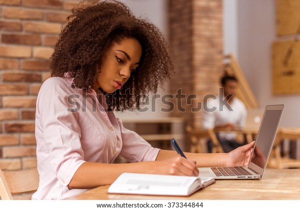 Young beautiful Afro-American businesswoman using laptop and writing in notebook while studying in cafe