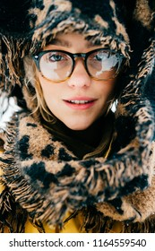 Young beautiful amazing cute attractive odd fancy bizarre unordinary girl closeup portrait. Lovely stylish fashionable female person in glasses. Strange woman in winter snowy forest. Soft tenderness.