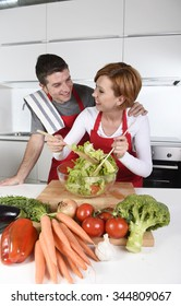 young beautiful American couple working at home kitchen wearing red apron mixing vegetable salad smiling happy in husband and wife cooking together healthy fresh food concept