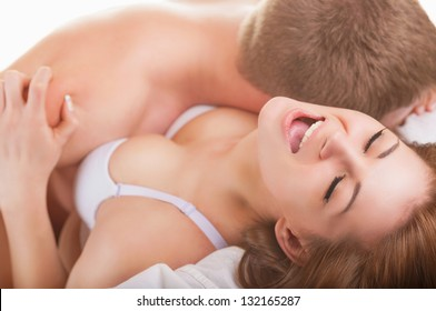 Young beautiful amorous couple making love in bed on dark background