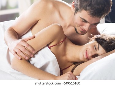 Young beautiful amorous couple making love in bed. Love, relationships and dating concept.