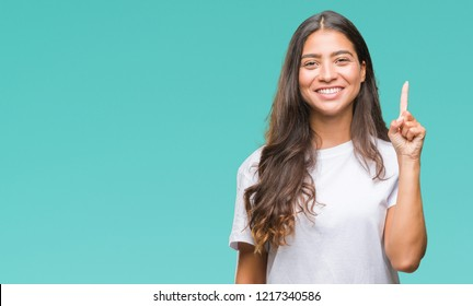 Young beautiful arab woman over isolated background showing and pointing up with finger number one while smiling confident and happy.