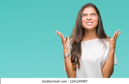 Young beautiful arab woman over isolated background crazy and mad shouting and yelling with aggressive expression and arms raised. Frustration concept.