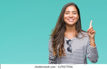 Young beautiful arab woman wearing sunglasses over isolated background showing and pointing up with finger number one while smiling confident and happy. - Shutterstock ID 1170177556