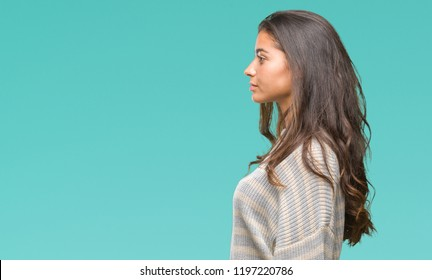 Young beautiful arab woman wearing winter sweater over isolated background looking to side, relax profile pose with natural face with confident smile.