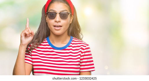 Young beautiful arab woman wearing sunglasses over isolated background pointing finger up with successful idea. Exited and happy. Number one.