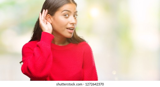 Young beautiful arab woman wearing winter sweater over isolated background smiling with hand over ear listening an hearing to rumor or gossip. Deafness concept.