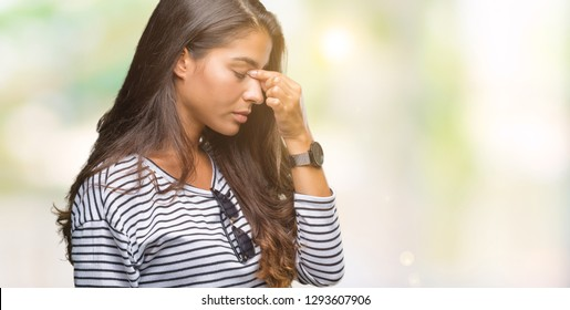 Young beautiful arab woman wearing sunglasses over isolated background tired rubbing nose and eyes feeling fatigue and headache. Stress and frustration concept.