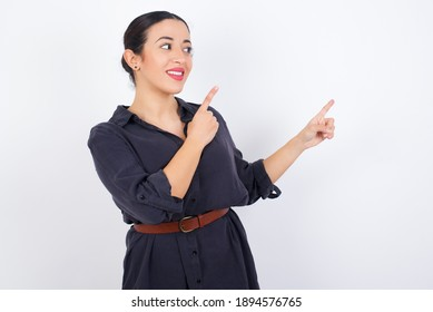 young beautiful Arab woman wearing gray dress against white studio background with positive expression, indicates with fore finger at blank copy space for your promotional text or advertisement.