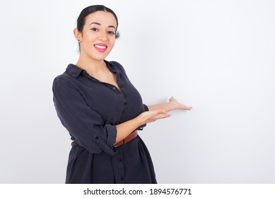 young beautiful Arab woman wearing gray dress against white studio background Inviting to enter smiling natural with open hands. Welcome sign.