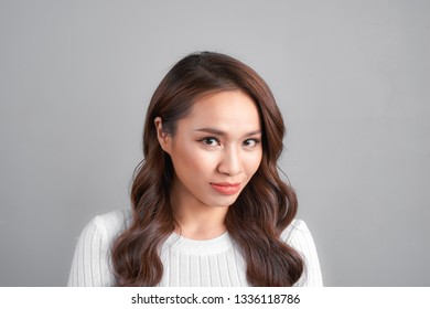 young beautiful arrogant and moody woman showing negative feeling and contempt facial expression isolated on grey background looking cocky and defiant