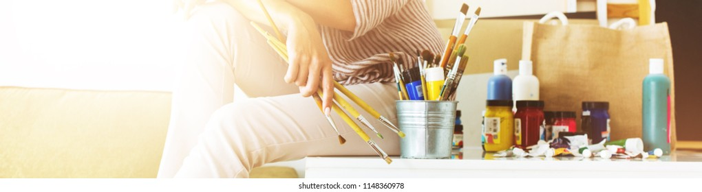 Young Beautiful Artist Painter Woman Sitting on Working Table in Her Home Office Businesswoman Entrepreneur Have Fun Freedom to Be Independent Long banner