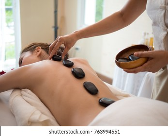 Young beautiful Asian or Asia  woman receiving hot stone massage and relaxing in spa salon
