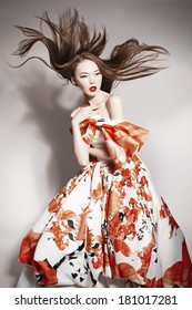young beautiful asian brunette in gorgeous dress, motion shot, flying hair