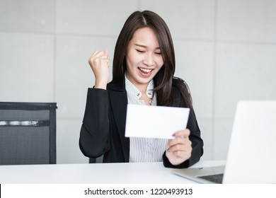 Young beautiful Asian business woman feeling happy or success after look at bonus money or salary in an envelop.