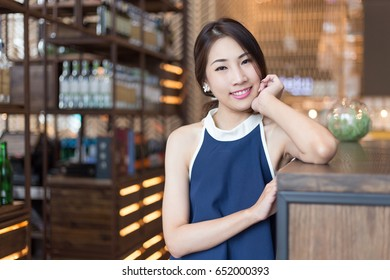 Young beautiful Asian business woman posing with luxury style while looking to the camera with smiling emotional