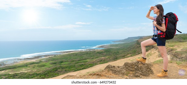 young beautiful asian female backpacker standing on top of hill looking at the coastal scenery