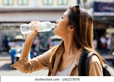 Young beautiful Asian female tourist woman drinking water from plastic bottle in city of Bangkok, Thailand
