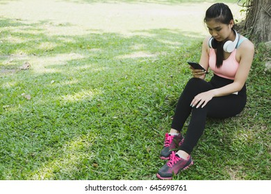 young beautiful asian fitness athlete woman with white headphones and smart phone relaxing and listening to music in the city park after jogging and exercise