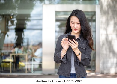 Young and beautiful Asian freelance business woman using a smartphone while walking on the street in the urban city