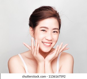 young beautiful asian girl with clean skin, Cosmetic Beauty Concept,hands touch on the cheek, smiling and friendly face isolated on grey background