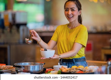 A young beautiful asian girl Enjoy eating shabu shabu with relaxing time food time of a Japanese restaurant by big set shabu shabu on table
