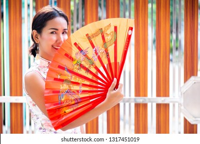 Young Beautiful Asian Girl Holding Chinese Traditional Style Fan with Qipao Dress. Happy and Smiley Face that Show the Power and Wealthiness.